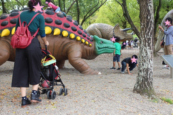 ① のんほいパーク. 自然史博物館前には、屋外に恐竜の遊具がたくさん。みんな、ジャングルジムのようにしてのぼったりつかまったりして遊んでいます。